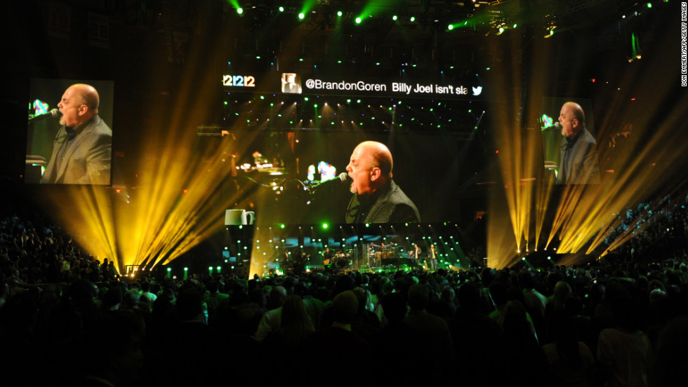Jumbo screens project multiple images of Billy Joel's performance.