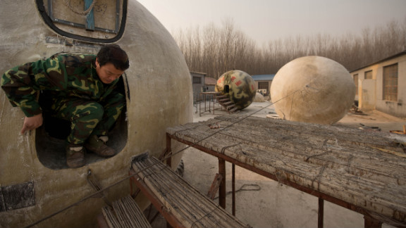 Liu climbs out of one of the pods that are sitting in his yard
