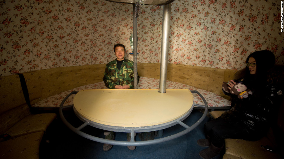 Liu and his daughter sit inside one of  the pods. The pods seat 14 people each and have varying interiors.