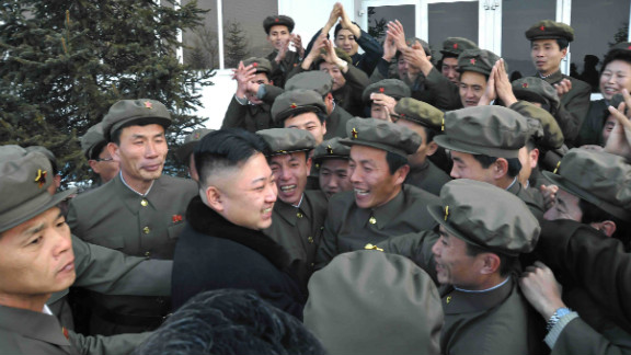 Well-wishers mob a smiling North Korean leader Kim Jong Un (without hat) on Wednesday after the successful launch of the country