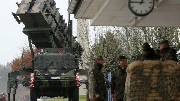 Soldiers of the Air Defence Missile Squadron 2 stand guard with Patriot missile launchers in the background in Bad Suelze, northern Germany on December 4, 2012.