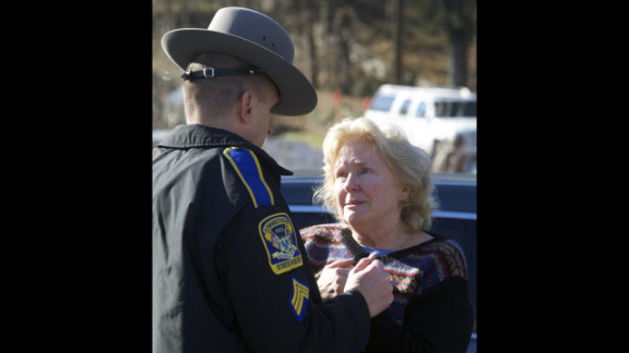 A woman speaks with a Connecticut state trooper outside Sandy Hook Elementary School on December 14.
