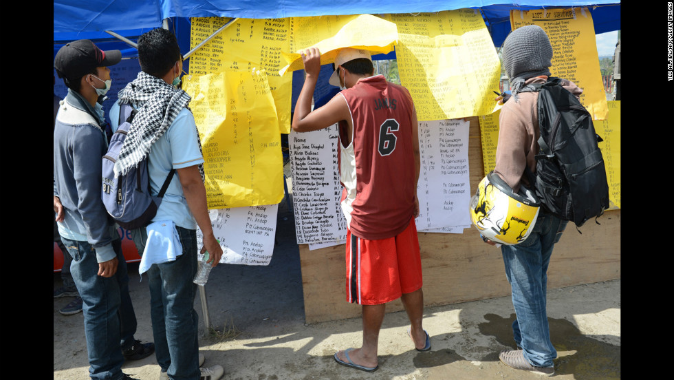 Residents look at the lists of missing relatives displayed near the municipal hall in New Bataan, Compostela province on Wednesday, December 12, nearly one week after the southern part of the Philippines was hit by Typhoon Bopha. Bopha, the strongest cyclone to hit the Philippines in decades, has taken more than 700 lives and hundreds remain missing, the government said on December 11. The United Nations launched a $65 million global appeal on December 10 to help survivors.