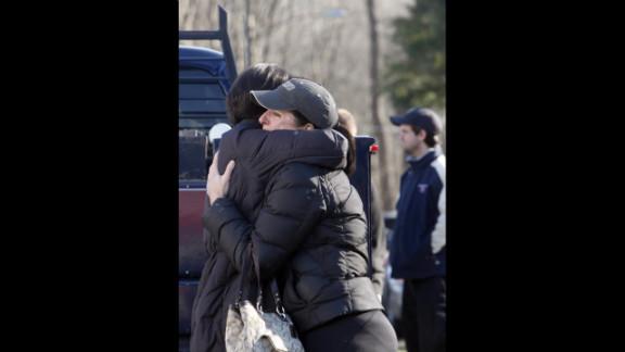 People embrace outside Sandy Hook Elementary School on December 14.