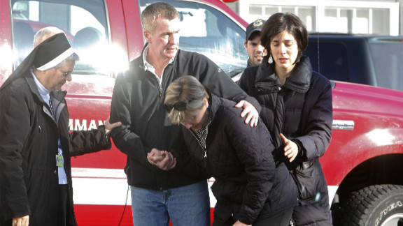 People try to deal with the shock of the attack outside Sandy Hook Elementary School on December 14.