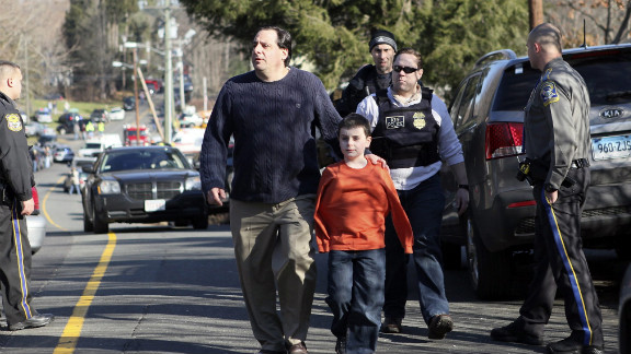A man escorts his son away from Sandy Hook Elementary School on December 14.