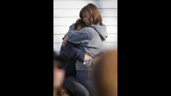 People comfort each other near Sandy Hook Elementary School on December 14.