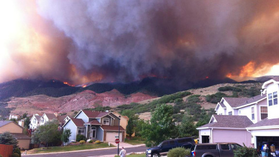 """Wildfires burning in the foothills of the Colorado Springs mountains blanketed a nearby neighborhood with pitch-black smoke in June. """"We ran outside and saw the side of the foothills getting engulfed by flames coming down on either sides of the quarry,"""" said photographer Michael Kennedy. """"Our subdivision quickly deteriorated into a war zone with police cars coming into the neighborhood with loud speakers announcing"""