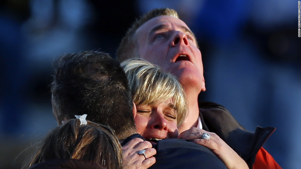 People weep and embrace near Sandy Hook Elementary School on Friday, December 14.