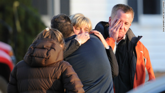 Unidentified people react on December 14, 2012 at the aftermath of a school shooting at a Connecticut elementary school that brought police swarming into the leafy neighborhood, while other area schools were put under lock-down, police and local media said. Local media quoted that the gunman had died at the Sandy Hook Elementary School in Newtown, Connecticut, northeast of New York City. At least 27 people, including 18 children, were killed on Friday when at least one shooter opened fire at an elementary school in Newtown, Connecticut, CBS News reported, citing unnamed officials. AFP PHOTO/DON EMMERT (Photo credit should read DON EMMERT/AFP/Getty Images)