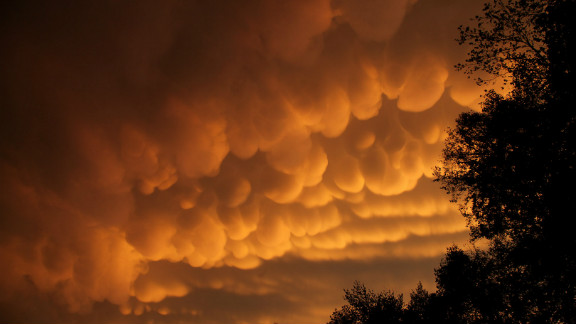 """Rare cloud formations, called mammatus, were spotted in La Crosse, Wisconsin in September. The name """"mammatus"""" comes from the Latin word manna, or breast. """"After the storms rumbled through, I saw a yellow orange glow out the window,"""" said Jim Jorstad. """"I then grabbed my camera, began driving several miles up the hill, stopping to take photos along the way."""""""