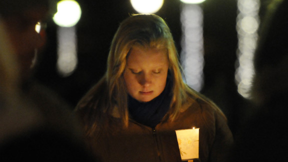 Corinne McLaughlin, a student at the University of Hartford, bows her head during a candlelight vigil at Hartford, Connecticut