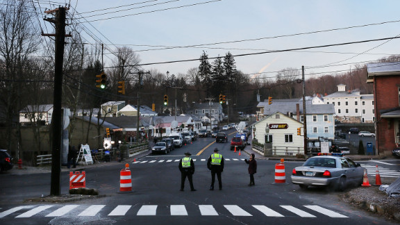 Police officers stand at the entrance to the street leading to the Sandy Hook Elementary School on December 15.