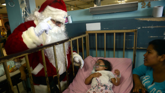 A man dressed as Santa Claus sees a patient in the pediatric ward of a hospital in Guatemala City, Guatemala, on Friday, December 14.