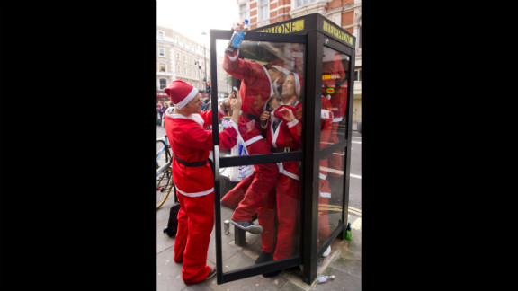 Costumed Santas crowd into a telephone booth during the Santacon pub crawl near London