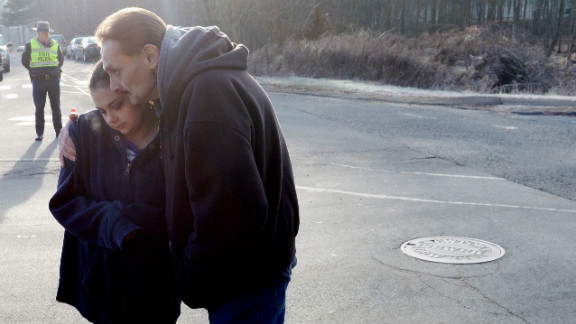 Ken Kowalsky and his daughter Rebecca, 13, embrace while standing at the end of the road leading to Sandy Hook Elementary School on Saturday.