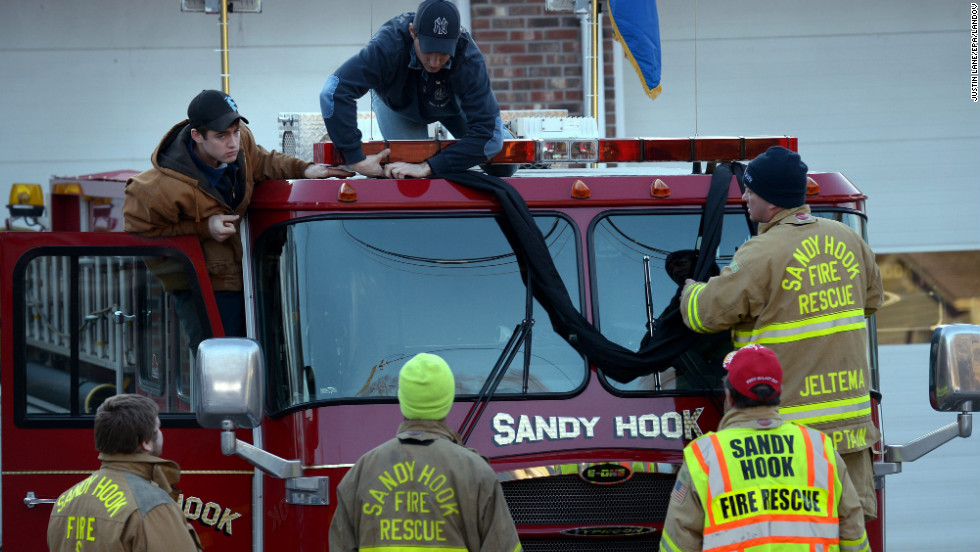 Firefighters attach black bunting to a fire truck as a memorial at the fire station down the street from the Sandy Hook Elementary School in Newtown, Connecticut, on Saturday, December 15.
