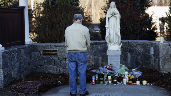 A man bows his head as he stands at a makeshift memorial, outside Saint Rose of Lima Roman Catholic Church in Newtown on Saturday, December 15.