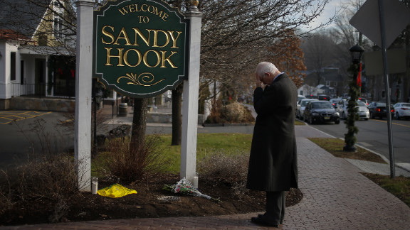 New Jersey resident Steve Wruble, who was moved to drive out to Connecticut to support local residents, grieves for victims at the entrance to Sandy Hook village in Newtown on Saturday.