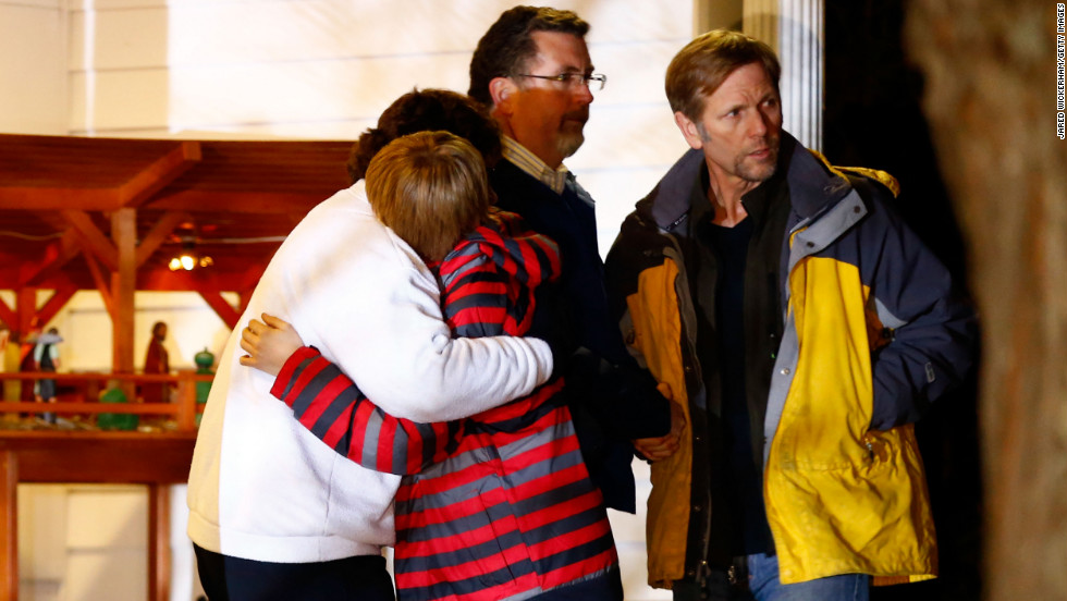 People hug outside of the Newtown United Methodist Church on Friday, near the site of the shootings at the Sandy Hook school.