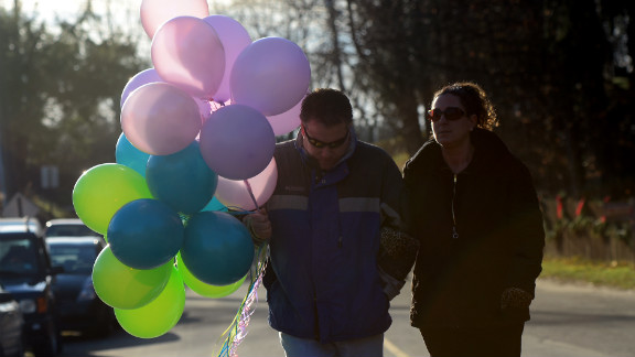 A couple carry balloons to place at a curbside shrine to in Newtown on Saturday.