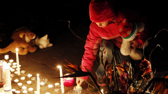 A child lights a candle at a memorial filled with flowers, stuffed toys and candles outside of Saint Rose of Lima Church near Sandy Hook Elementary School in Newtown, Connecticut on Saturday.