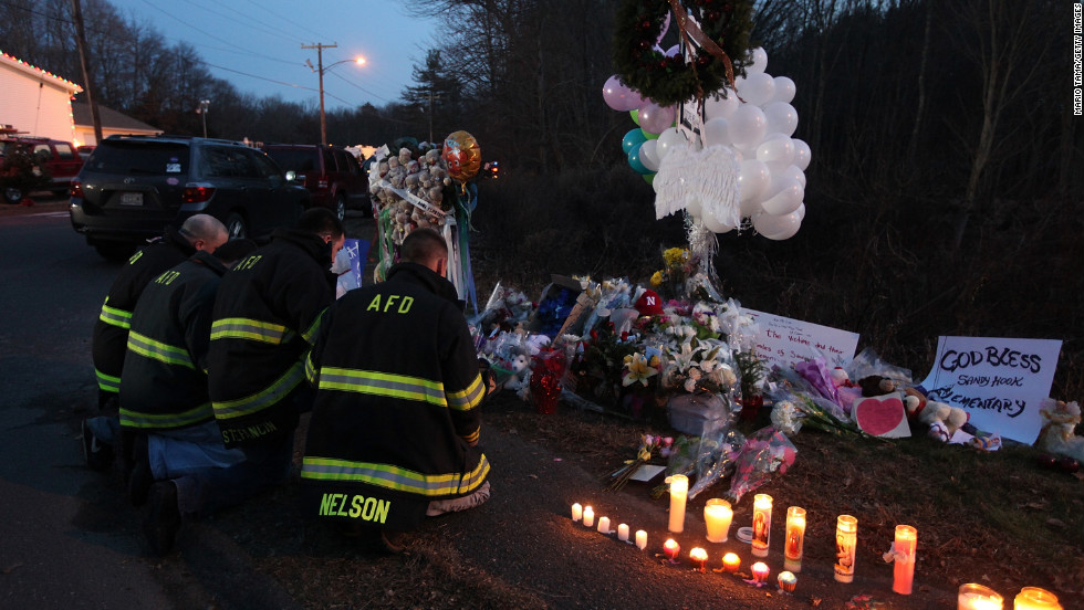 Firefighters kneel to pay their respects at a makeshift memorial near the school in Newtown on Saturday.