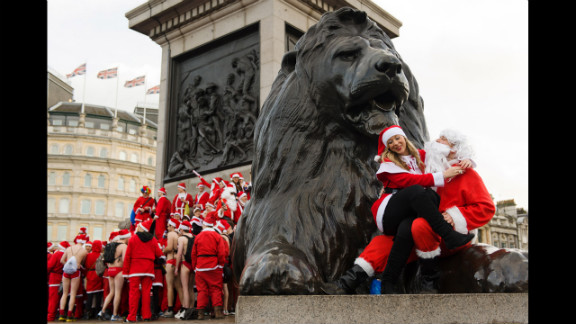 Revelers in Santa costumes sit on the lion statue at the base of Nelson