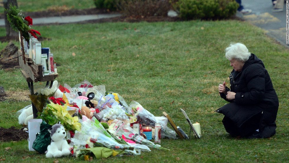A parishioner kneels in front of a makeshift memorial at St. Rose of Lima Roman Catholic Church in Newtown on December 16.