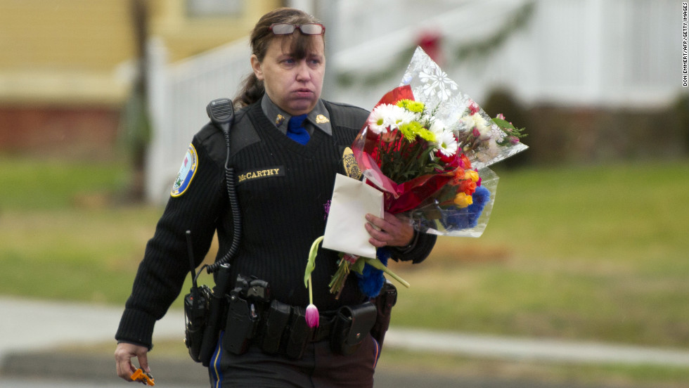 A police officer removes flowers from a busy intersection on December 16 in Newtown. Police said they were afraid the memorial, left for the victims of the Sandy Hook Elementary School shooting, would cause a traffic hazard.