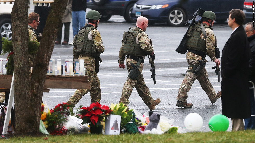 Connecticut State Police officers search outside St. Rose of Lima Roman Catholic Church in Newtown, Connecticut, on Tuesday, December 16, after a threat prompted authorities to evacuate the building. Investigators found nothing to substantiate the reported threat, a police official said, declining to provide additional details. The church held Sunday services following the mass shooting at Sandy Hook Elementary School in Newtown.