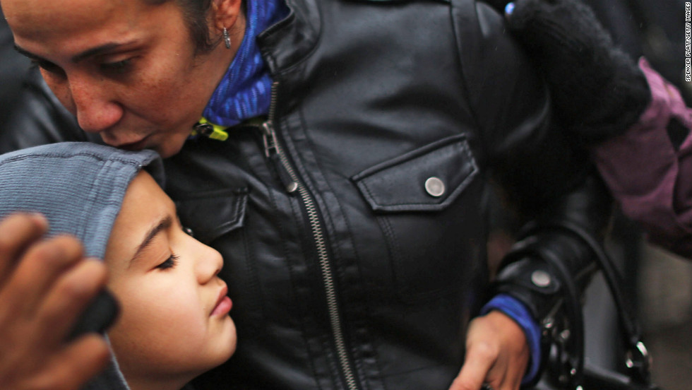 Ty Diaz is kissed by his mother, Yvette, at a memorial down the street from Sandy Hook on December 16.