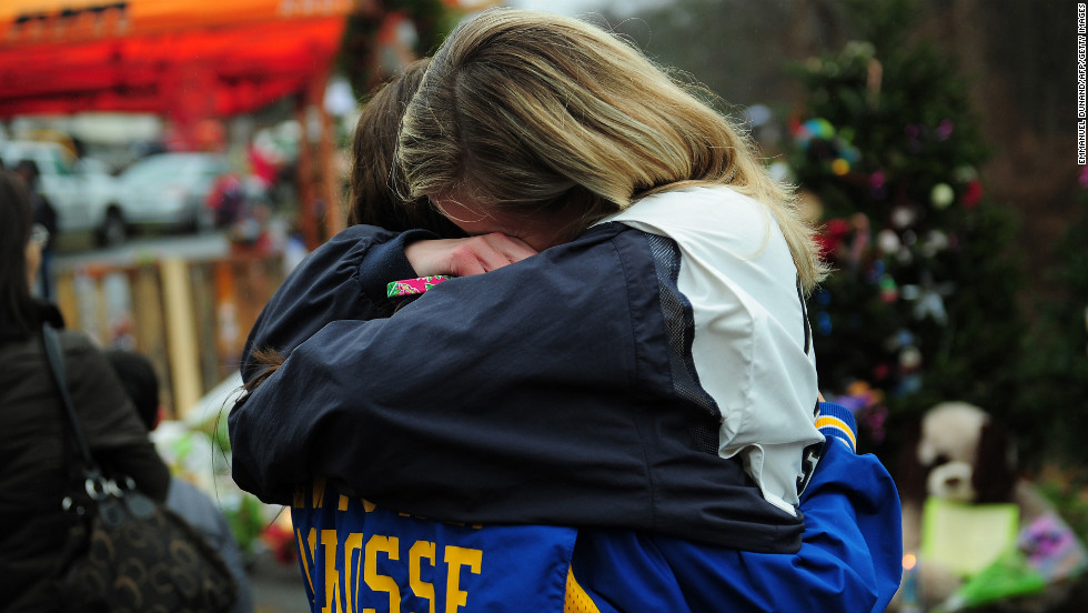 Two teenagers embrace at a makeshift shrine to the victims in Newtown on December 16.