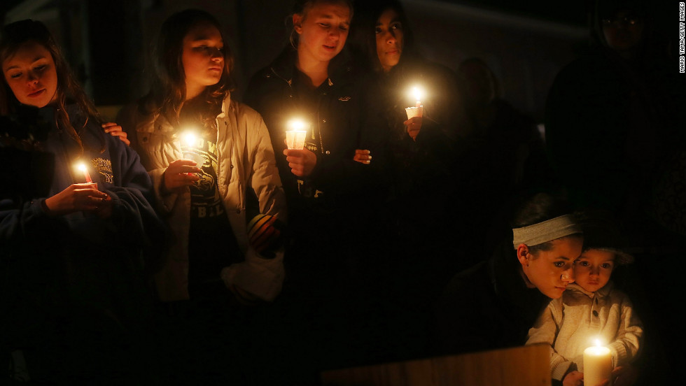 From left: Newtown residents Claire Swanson, Kate Suba, Jaden Albrecht, Simran Chand and New London, Connecticut, residents Rachel Pullen and her son, Landon DeCecco, hold candles at a memorial for victims on Sunday, December 16, in Newtown, Connecticut.