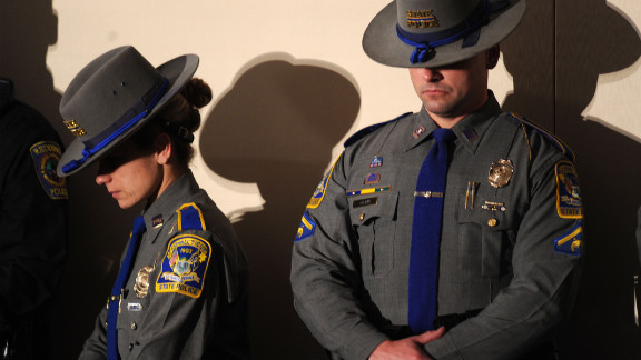 Connecticut state troopers bow their heads during the interfaith vigil.