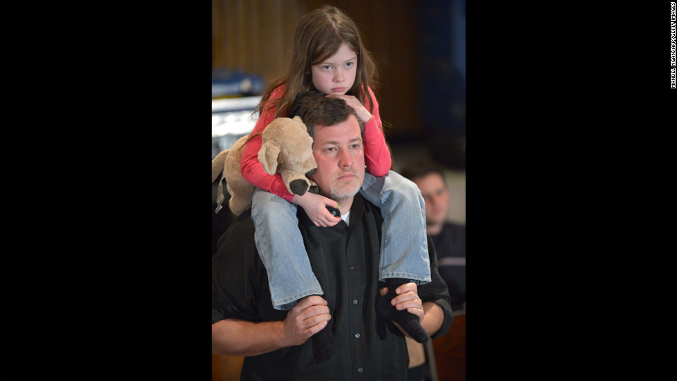 A little girl clutches a plush toy dog as she rides on her father's shoulders into the Newtown High School auditorium.