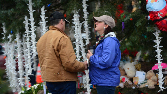 People pay their respects on December 17 at a makeshift shrine in Newtown to the victims of Friday
