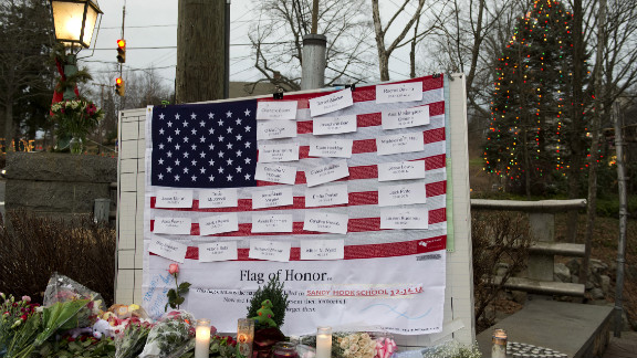 Names of victims are displayed on a flag in the business area of Newtown, Connecticut, on December 16.