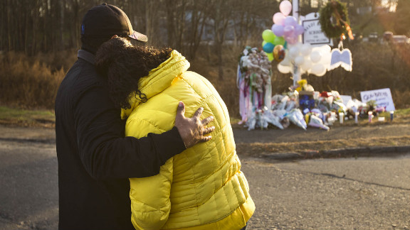 Two people embrace near a makeshift memorial in Newtown, Connecticut, on Saturday, December 15.