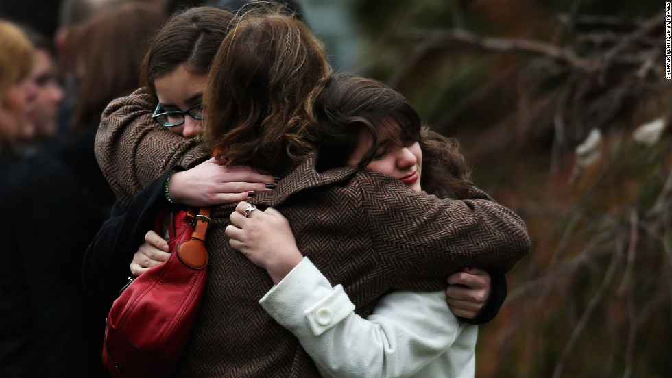 Three women embrace as they arrive for the funeral services for Noah Pozner on December 17.