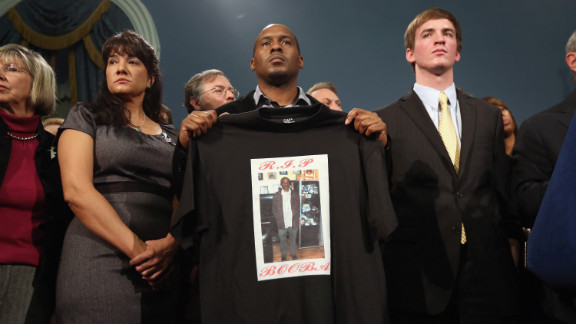 Chris Foye, whose son Chris Owens was killed by a stray bullet in 2009, stands with other survivors and family members of gun violence at Bloomberg