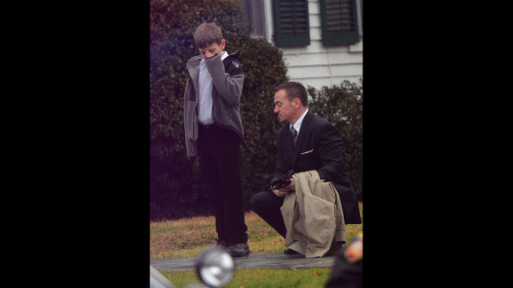 A man comforts a young mourner at Honan Funeral Home while attending the funeral for Jack Pinto, 6, on December 17.