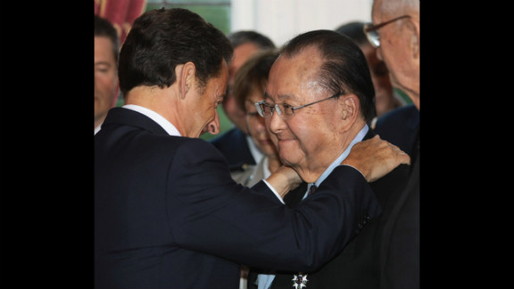 French President Nicolas Sarkozy, left, embraces Inouye after awarding him the Legion d