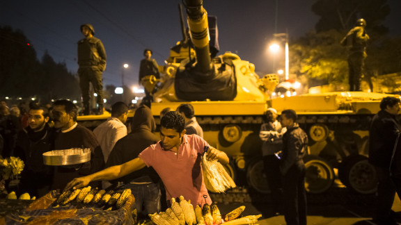 A street vendor grills corn as Egyptian soldiers stand guard at the Presidential Palace on Tuesday, December 18, in Cairo. Protesters opposed to President Mohamed Morsy