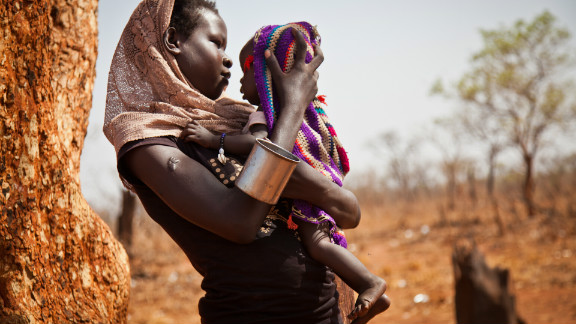 """A woman and her child from the Nuba Mountains wait outside the Yida refugee camp registration center. """"There is no such thing as pens or notebooks for the thousands of children in need of an education at Yida,"""" says Nyange."""