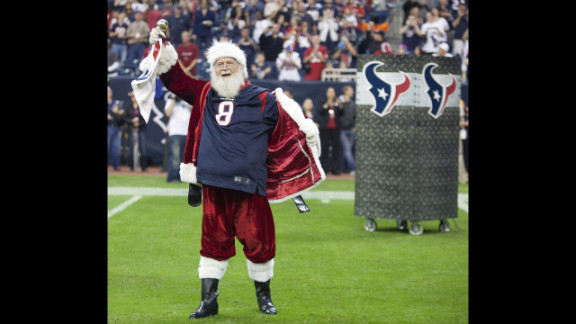 Santa Claus opens his coat to reveal a Matt Schaub jersey at Reliant Stadium on Sunday, December 16, in Houston, Texas, before the Texas Longhorns played the Indianapolis Colts.