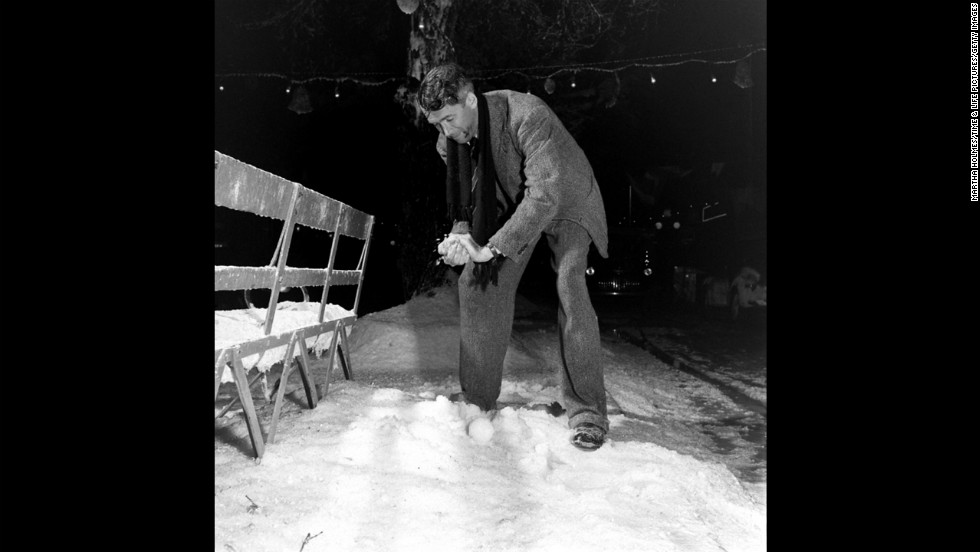 "Actor Jimmy Stewart packs a snowball on the set of ""It's a Wonderful Life."" In the 1946 holiday classic, an angel shows frustrated businessman George Bailey what his community would have been like without him."