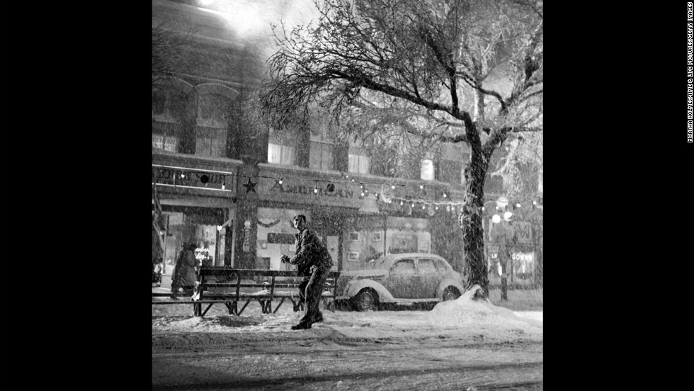 "Jimmy Stewart enjoys the falling ""snow"" in downtown Bedford Falls, the fictional town in the movie."