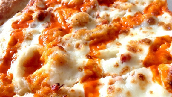 Papa John's Buffalo Chicken Pizza: Creamy ranch and buffalo sauce, cheese, bacon, and pizza dough are the likely sodium culprits in this chicken-encrusted pie. One slice of a large, original crust -- 1/8th of an order -- has 1,050 milligrams of sodium and 370 calories. But you know you'll go for two slices, if not more.