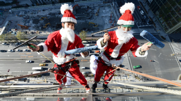 Two Japanese Santas clean the windows of a Tokyo hotel on December 20.